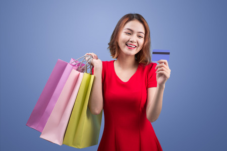 Santa asian woman holding shopping bags and credit card against violet