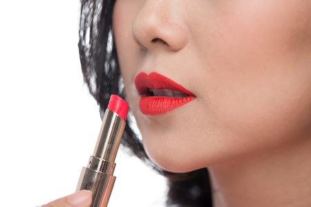かなりアジアの若い女性が彼女の唇に赤のマットの口紅を適用します。