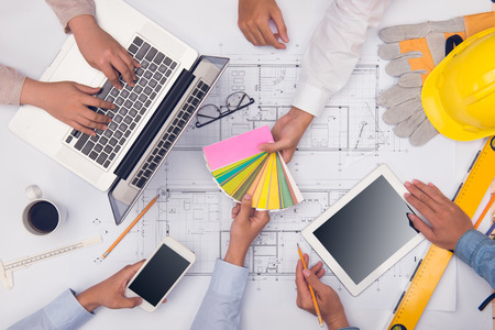 Hands of professional architects discussing and working with blueprints Stock Photo