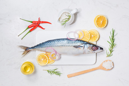 Fish dish cooking with various ingredients. Fresh raw fish decorated with lemon slices and herbs on wooden table. Stock Photo - 84280224