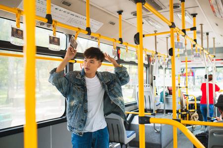 Asian man taking public transport, standing inside bus.