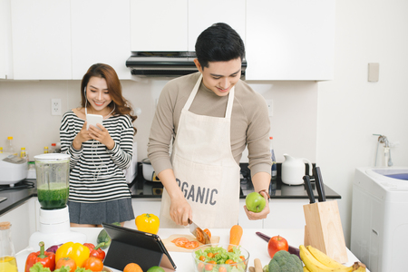 Asian woman using cell phone while a man prepares a meal Banco de Imagens