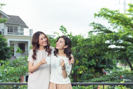 행복한 젊은 여자 친구가 함께 서있는 동안 잘 입고 웃는