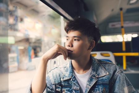 電車やバスの窓から屋外の景色を考えているアジア人男性旅行者。
