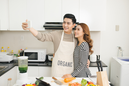 Happy asian couple smiling and cooking in the kitchen doing selfie using a smart phone