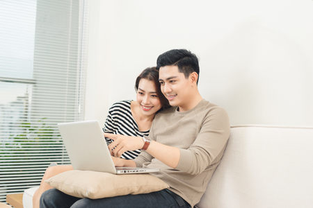 Young asian couple surfing on internet with laptop.