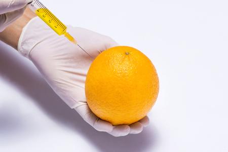 Science experiment with orange and syringe isolated on white. Stock Photo