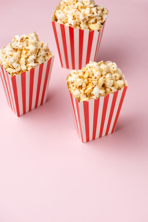 Popcorn in red and white cardboard box on the pink background. 版權商用圖片