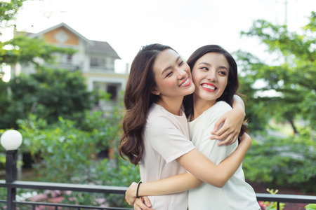 Heureuses jeunes femmes amies bien habillées souriantes tout en restant debout ensemble