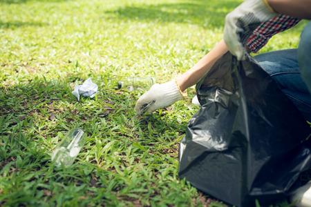 Jonge man buigen om te vallen en op te halen in vuilniszak