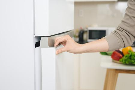 男性の手は白い冷蔵庫のドアを開いてください。