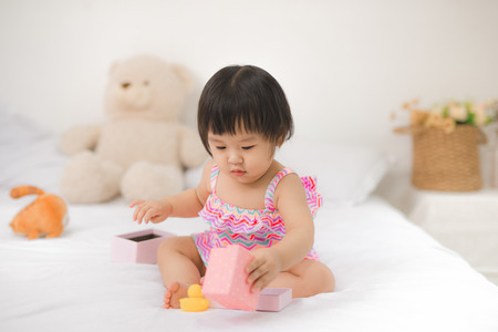 Weinig schattige Aziatische baby meisje zittend op bed spelen