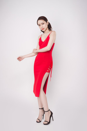 Beautiful stylish asian woman wearing red dress on grey background. Stock Photo