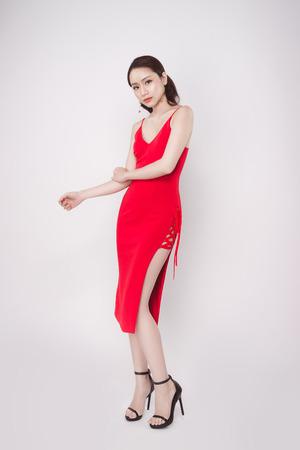 Hermosa mujer asiática con estilo vestido rojo sobre fondo gris.