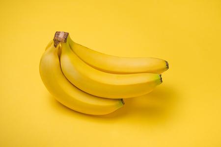 黄色の背景にバナナの花束。 写真素材