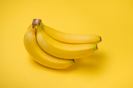 A banch of bananas on yellow background.