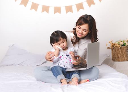 Asian lady in classic suitvworking on laptop at home with her baby girl chatting with father. Фото со стока