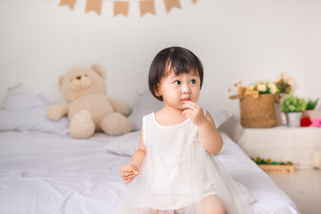 Cute little girl eating cookie at home