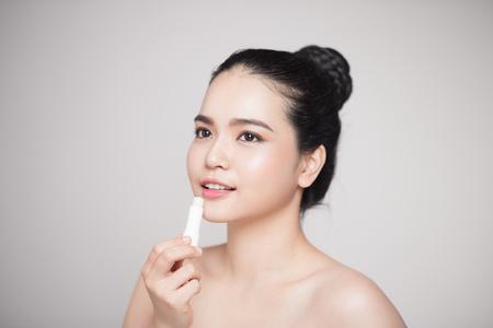 Aziatische vrouw aan te passen hygiënische lippenbalsem over grijze achtergrond Stockfoto