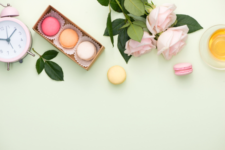 French macaroons. Many variegated sweet macarons in box with bouquet of pink roses on the table