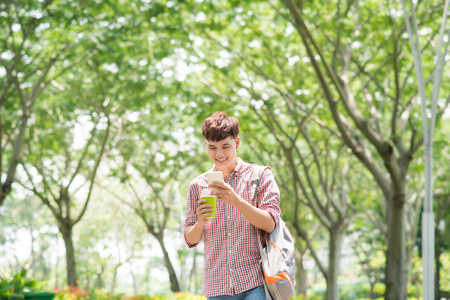 Young handsome Asian man enjoying his smart phone in public park
