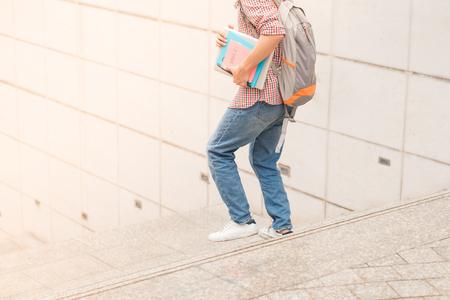 Bebouwd beeld van mannelijke student die met boek in handen loopt