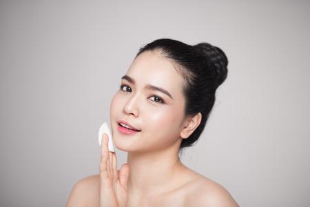 행복 한 미소 아름 다운 아시아 여자 피부를 청소하는 면화 패드를 사용 하여 웃 고.