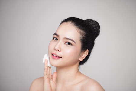 Happy smiling beautiful asian woman using cotton pad cleaning skin. Banco de Imagens