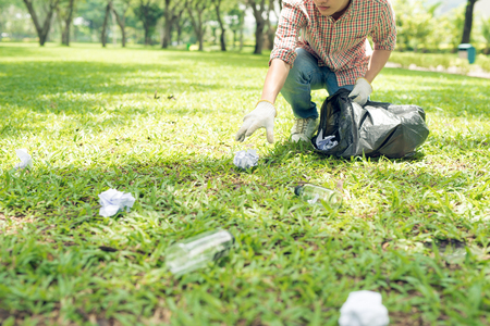 Joven agachándose a desperdiciar y recogiendo en bolsa de basura Foto de archivo - 84575456
