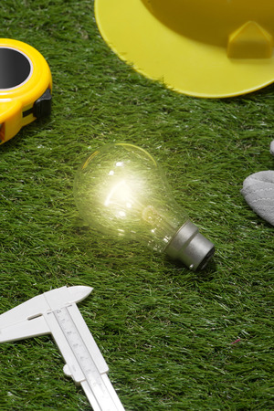 House engineer and architect ideas concept with light bulb. Yellow hat and tools on green grass background