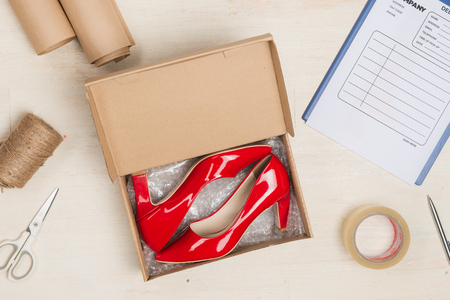 Stylish womans shoes in a box on wooden table.