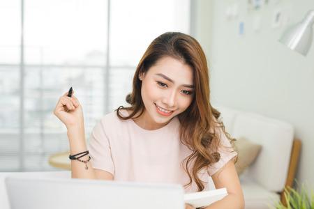 Jonge mooie Aziatische vrouw die thuis werkt Stockfoto - 84873257