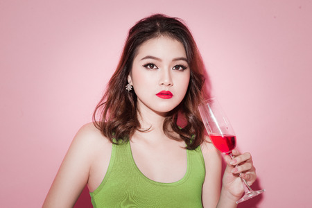 Celebrating asian girl with professional makeup holding a glass of champagne.