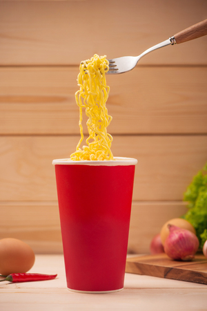 Eating Instant noodles in cup with a fork