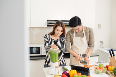 Portrait of happy asian young couple cooking together in the kitchen at home.