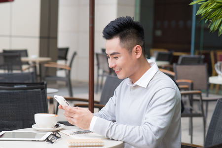 Young asian business man using phone in coffee shop