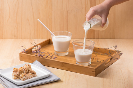 Dairy products. A bottle of milk and glass of milk serve with almond candies on a wooden table.