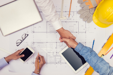 Hands of professional architects discussing and working with blueprints Stockfoto
