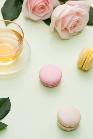 프랑스 마카롱. 테이블에 분홍색 장미 꽃다발과 상자에 많은 잡색 된 달콤한 마카롱