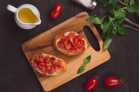 Simple italian appetizing bruschetta with tomato, on wooden table