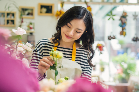 Pretty young florist with bouquet in flower shop Stok Fotoğraf - 84914804