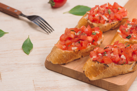 Italian bruschetta with roasted tomatoes, mozzarella cheese and herbs on a cutting board Banco de Imagens