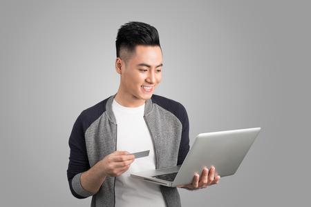 ノート パソコンと分離されたスタジオ背景が灰色でクレジット カードと若いアジア男