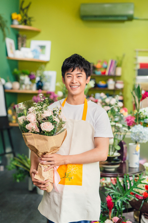 Handsome male florist is standing in flower shop and holding bouquet of flowers Stockfoto