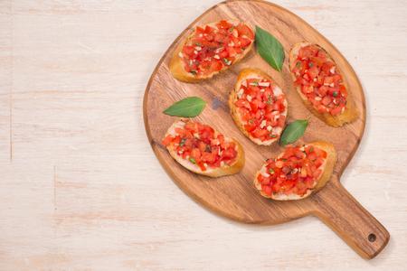 Italiaanse bruschetta met geroosterde tomaten, mozarellakaas en kruiden op een snijplank Stockfoto