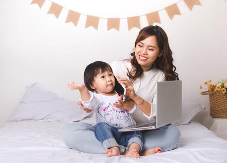Aziatische dame in het klassieke suitvworking op laptop thuis met haar babymeisje die met vader babbelen.