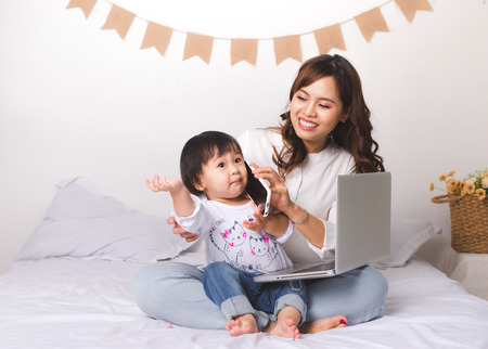 Asian lady in classic suitvworking on laptop at home with her baby girl chatting with father. Foto de archivo