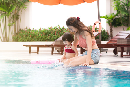 Mother and baby girl having fun in the pool. Summer holidays and vacation concept Reklamní fotografie