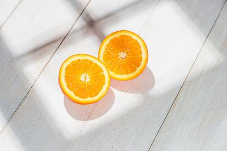 Half of orange on white wooden table.