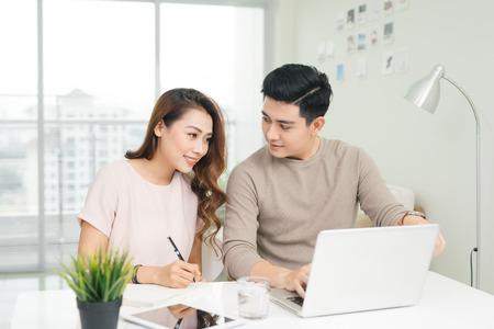 행복 한 젊은 커플 읽기 및 테이블에 앉아 법안을 분석합니다. 가정 경제를 논의하는 캐주얼의 젊은 부부 스톡 콘텐츠